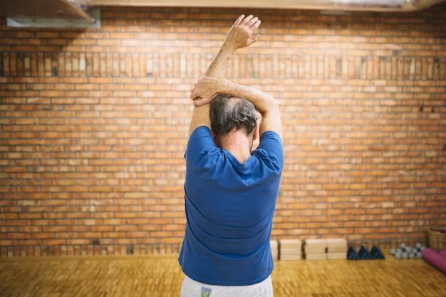Homme qui s'étend dans la salle de gym