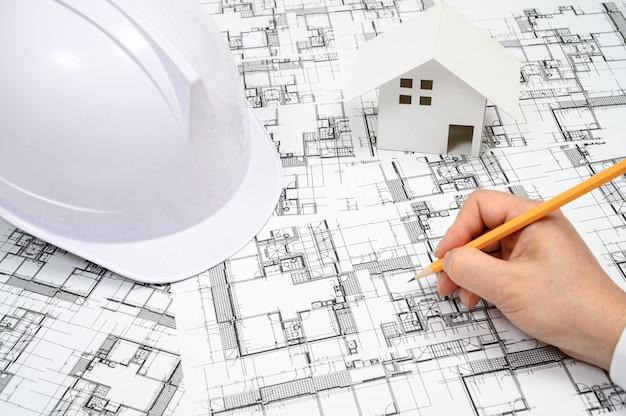 Un homme qui tient un crayon dans sa main et peint des dessins d'architecture