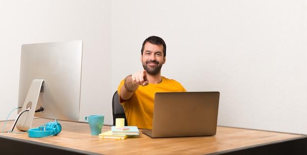 Un homme qui travaille avec laptot dans un bureau pointe le doigt vers vous avec une expression confiante