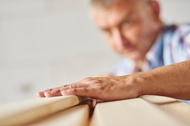 Un homme qui travaille très dur mesure une autre planche de bois