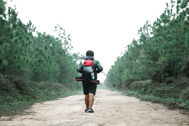 Homme qui voyage avec backpacker dans la forêt