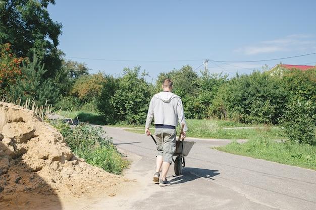 Un homme de race blanche de 30 ans porte une brouette de jardin pour charger du sable afin de remplir les chemins de béton dans son chalet d'été