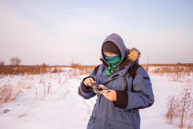 Homme de race blanche de 30 ans volant drone dans le champ enneigé en hiver.