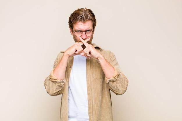 Homme de race blanche adulte blonde à la grave et mécontent avec les deux doigts croisés à l'avant dans le rejet, demandant le silence