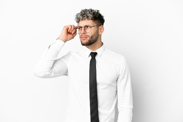 Homme de race blanche d'affaires isolé sur fond blanc ayant des doutes et avec une expression de visage confuse