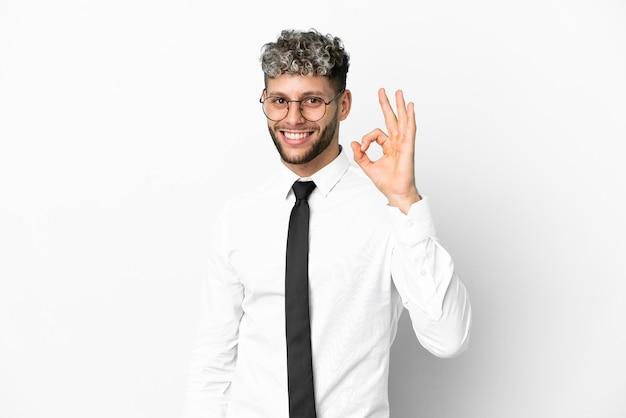 Homme de race blanche d'affaires isolé sur fond blanc montrant signe ok avec les doigts