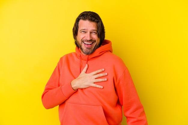 Homme de race blanche d'âge moyen isolé sur mur jaune rit bruyamment en gardant la main sur la poitrine