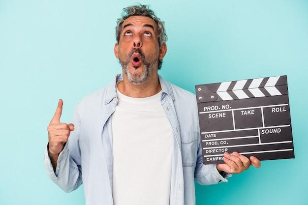 Homme de race blanche d'âge moyen tenant un clap isolé sur fond bleu pointant vers le haut avec la bouche ouverte.