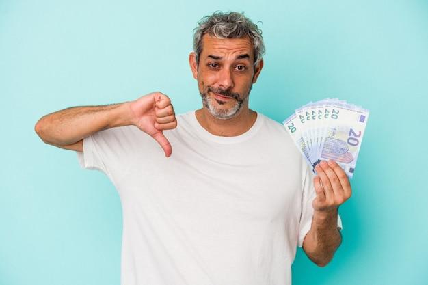 Homme de race blanche d'âge moyen tenant des factures isolées sur fond bleu montrant un geste d'aversion, les pouces vers le bas. notion de désaccord.