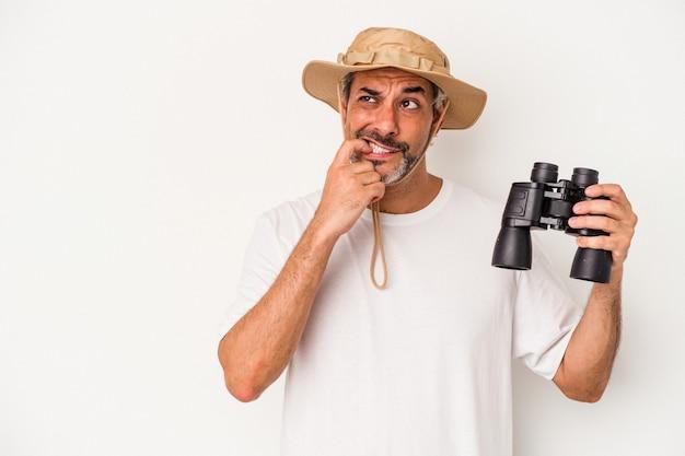 Homme de race blanche d'âge moyen tenant des jumelles isolées sur fond blanc détendue en pensant à quelque chose en regardant un espace de copie.