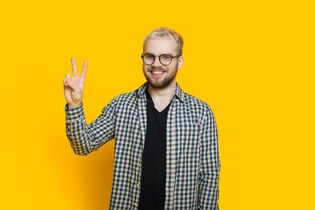 Homme de race blanche aux cheveux blonds et barbe courte fait des gestes de salutation avec ses doigts tout en posant sur un mur jaune