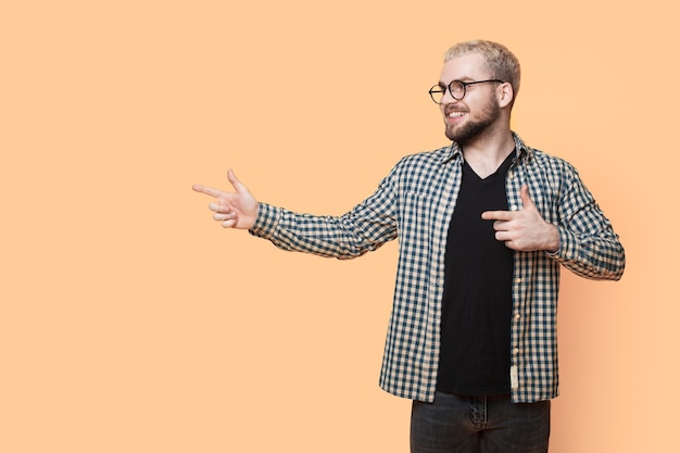 Homme de race blanche aux cheveux blonds et à la barbe porte des lunettes et pointant sur un mur jaune avec un espace libre
