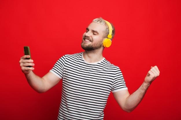 Homme de race blanche aux cheveux blonds dansant sur un mur rouge tout en écoutant de la musique avec des écouteurs