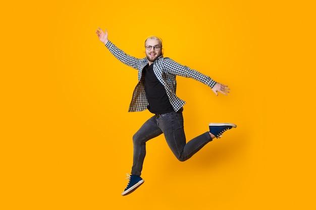 Homme de race blanche aux cheveux blonds et lunettes sautant sur un mur jaune tout en écoutant de la musique et sourire