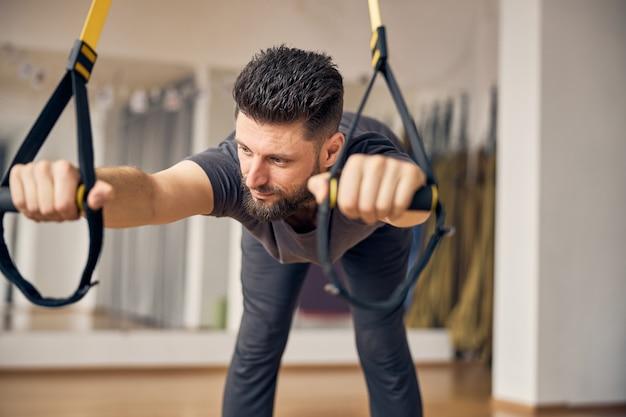 Homme de race blanche aux cheveux courts flexible et rêveur faisant des exercices de charnière de hanche à position large dans une salle de sport