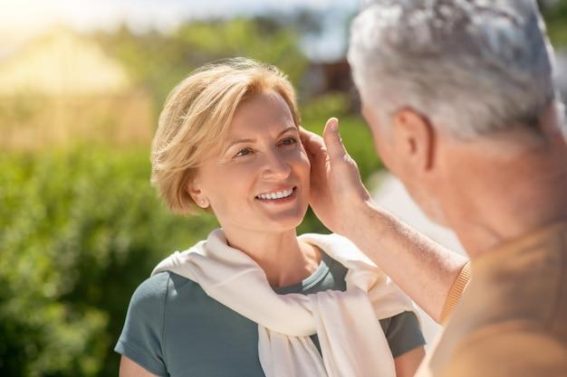 Homme de race blanche aux cheveux gris caressant le visage de sa belle femme blonde heureuse souriante d'âge moyen