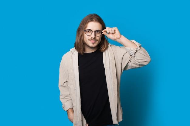 Homme de race blanche aux cheveux longs et barbe touche ses lunettes en souriant à la caméra sur un mur de studio bleu