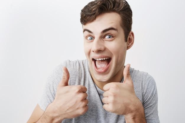 Homme de race blanche aux cheveux noirs musclé positif en t-shirt gris montrant des coups et sourit joyeusement avec la bouche ouverte, démontrant ses dents blanches et uniformes. les gens, les expressions du visage et les gestes.