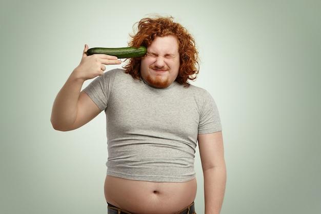 Homme de race blanche aux cheveux roux portant un t-shirt sous-dimensionné tenant le concombre à sa tempe comme une arme à feu