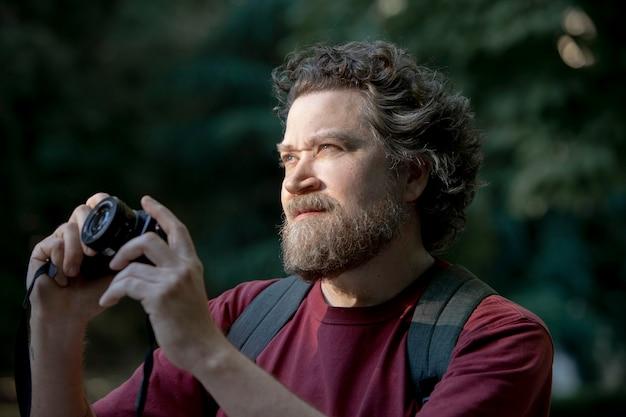 Homme de race blanche avec barbe et appareil photo à la main dans le parc