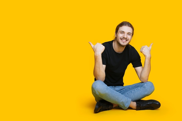 Homme de race blanche avec barbe et cheveux longs assis sur le sol et faisant des gestes le signe similaire près de l'espace libre de studio jaune