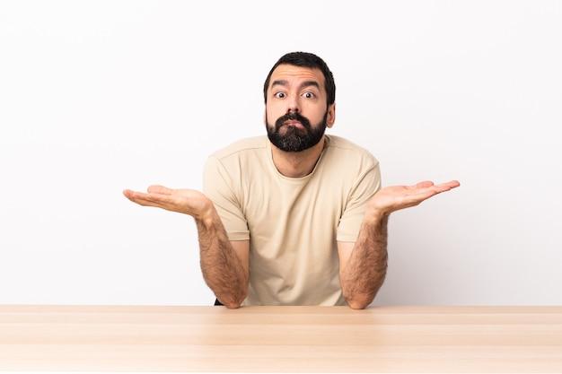 Homme de race blanche avec barbe dans une table ayant des doutes tout en levant les mains.