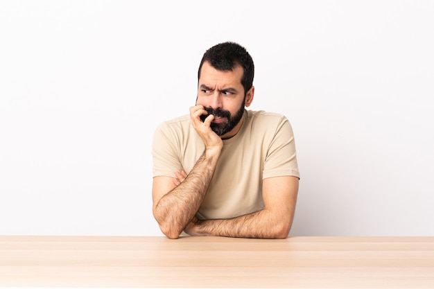 Homme de race blanche avec barbe dans une table ayant des doutes.