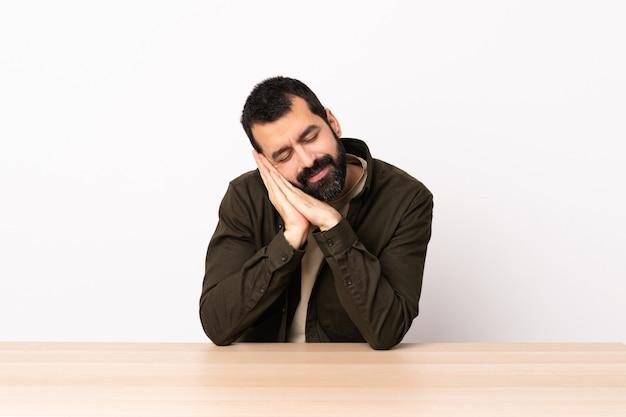 Homme de race blanche avec barbe dans une table faisant un geste de sommeil dans une expression dorable.