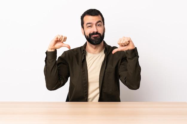 Homme de race blanche avec barbe dans une table fier et satisfait de soi.