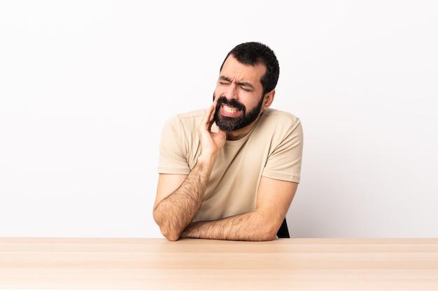 Homme de race blanche avec barbe dans une table avec mal de dents.