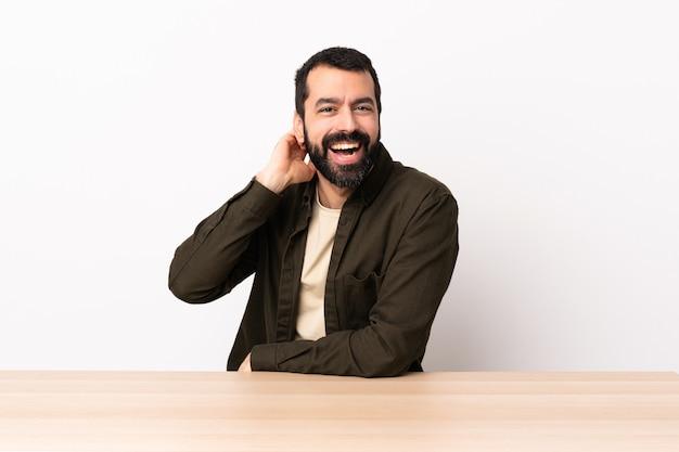 Homme de race blanche avec barbe dans une table en riant.