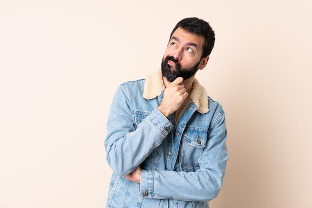 Homme de race blanche avec barbe sur mur ayant des doutes