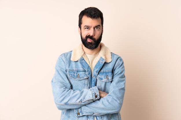 Homme de race blanche avec barbe sur mur isolé se sentir bouleversé