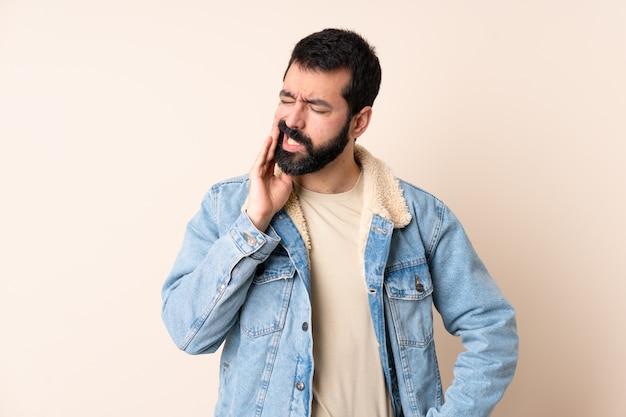 Homme de race blanche avec barbe sur mur avec mal de dents