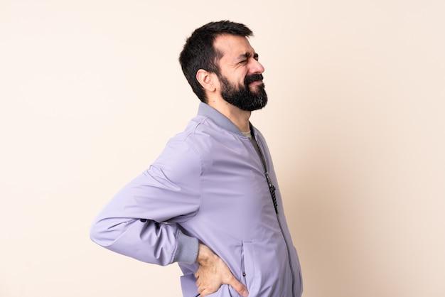 Homme de race blanche avec barbe portant une veste sur isolé souffrant de maux de dos pour avoir fait un effort