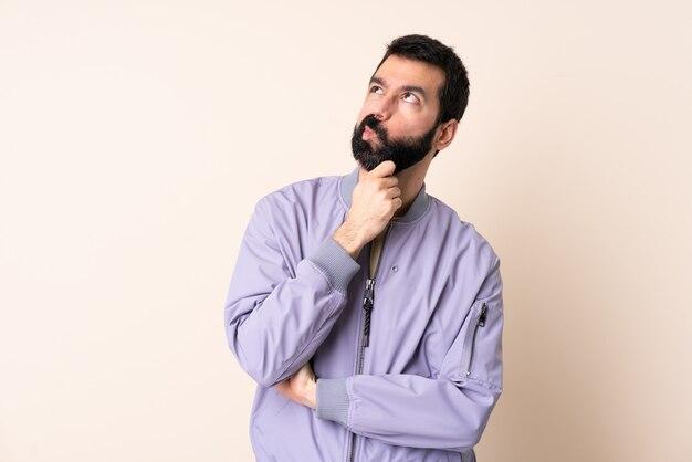 Homme de race blanche avec barbe portant une veste sur le mur ayant des doutes