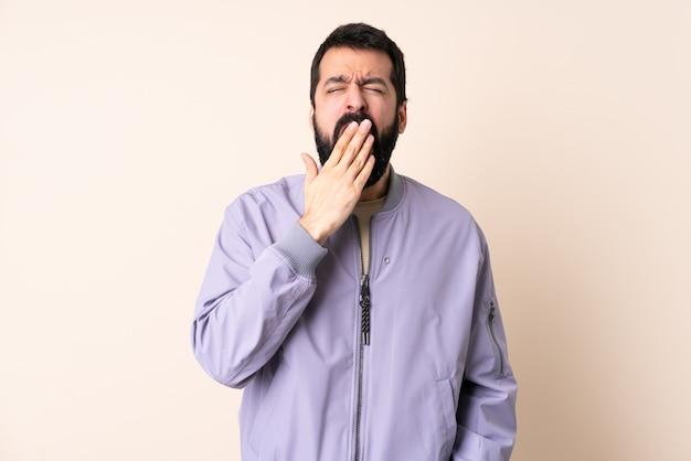 Homme de race blanche avec barbe portant une veste sur mur isolé le bâillement et couvrant la bouche grande ouverte avec la main