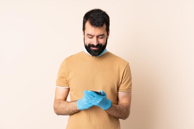 Homme de race blanche avec barbe protégeant contre le coronavirus avec un masque et des gants sur le mur en envoyant un message avec le mobile