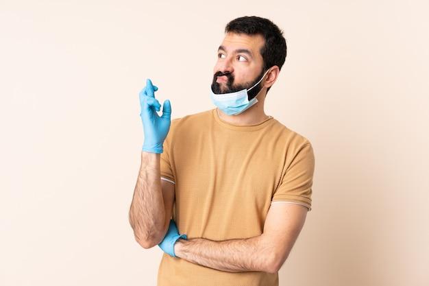 Homme de race blanche avec barbe protégeant avec un masque et des gants sur le mur avec les doigts traversant et souhaitant le meilleur