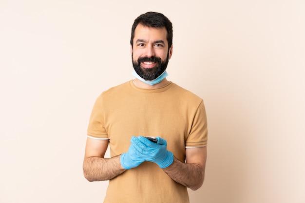 Homme de race blanche avec barbe protégeant avec un masque et des gants sur le mur en envoyant un message avec le mobile