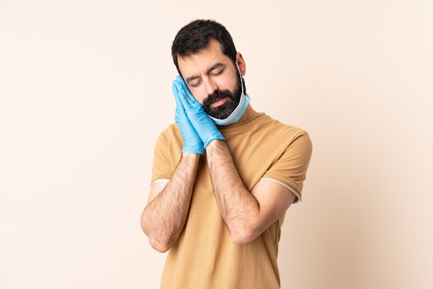 Homme de race blanche avec barbe protégeant avec un masque et des gants sur le mur faisant un geste de sommeil dans une expression adorable