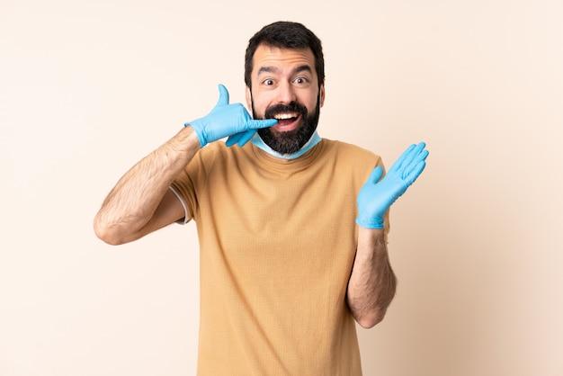 Homme de race blanche avec barbe protégeant avec un masque et des gants sur le mur faisant un geste de téléphone et doutant