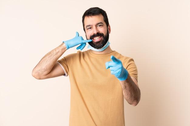 Homme de race blanche avec barbe protégeant avec un masque et des gants sur le mur faisant un geste de téléphone et pointant vers l'avant