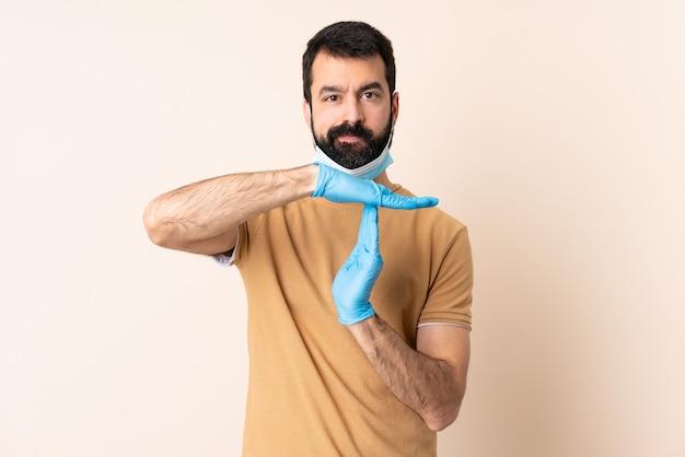 Homme de race blanche avec barbe protégeant avec un masque et des gants sur le mur faisant un geste de temporisation