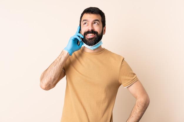 Homme de race blanche avec barbe protégeant avec un masque et des gants sur le mur, gardant une conversation avec le téléphone mobile