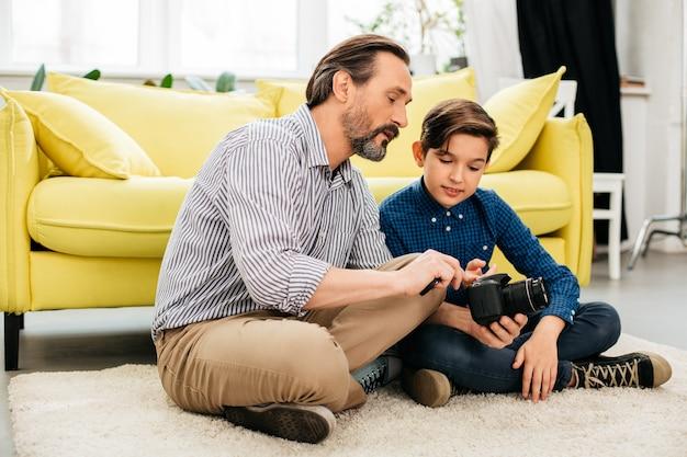 Homme de race blanche barbu assis sur le tapis moelleux à la maison et montrant à son fils les paramètres de la nouvelle caméra