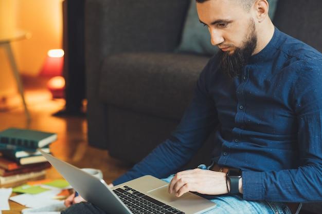 Homme de race blanche concentré vêtu d'une chemise bleue et portant une belle barbe travaille à son ordinateur et fait du travail sur papier