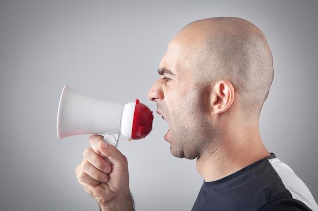 Homme de race blanche criant avec un mégaphone.