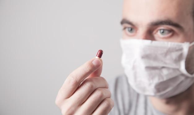 Homme de race blanche dans un masque médical montrant la pilule.