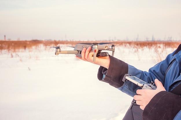 Homme de race blanche dans la veste bleue lançant un drone volant avec une télécommande à la main sur le terrain d'hiver.